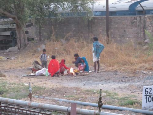 駅の近くで火を焚いて温まる家族。<br />格差。