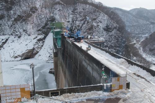 いつもの小旅行だと、あちこちで撮影したいがために早朝に自宅を出ることが多いのだが、今回はもっぱら雪見の温泉三昧なので、午前遅くに出発。途中、川治温泉を通りすぎてしばらく行くと五十里(いかり)ダムがあるのだが、ここが栃木県ではちょっとした話題になっている。このダムは1956年に完成したのだが、すでに60年以上経ち、放水路も旧式で放水量のコントロールができないため、ダムの壁に穴をあけて放水量を自在に制御できる新しい放水路を建設中なのである。