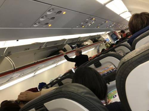 飛行機の中の様子。ほぼ満席で、ビジネスマンの姿は少なめで、ビーチリゾートに行くような人と大手旅行会社のツアーに参加するような人が混在していました。