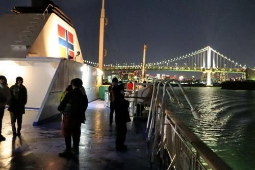 寒さの中、多くの人がデッキで夜景を楽しんでいます。