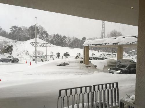 翌日4日の朝に迎えに来た、雪に囲まれた「いこいの村」玄関の車。スキー客には最適の大雪も、雪に迷惑を受けていると感じている僕には大トラブルである。