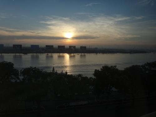 ベトナム3日目の朝。<br /><br />窓から見える 朝焼けの空と川面。
