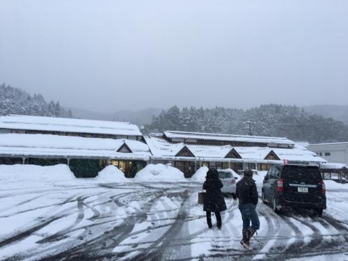 雪で覆われている石見田所駅前の様子。駅前の車道は、雪が取り除かれている。道の駅前が、屋根から落ちた雪で窓が塞がっている。建物で買い物ができるように、また田所駅で休むことができる様に出入口が除雪してある。中の店では、現地栽培野菜を直接農家が売っており、お菓子も現地産紅芋をから揚げした物等買うことができる。