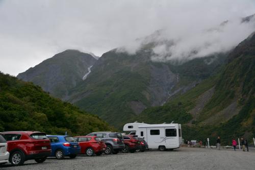 フォックス氷河の駐車場です。<br />雲行きが悪く雨が降り出しました。<br />そんなにひどくなりそうもないのでしばらく休んでいました。<br />
