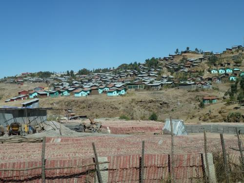 空港からは迎えのバスで町に向かいます。くねくねとした坂道を約30分上って、標高2600mのラリベラの町に到着。<br /> 途中、山の斜面に青い屋根の集落が見えてきますが、かって岩窟教会周辺に住んでいた人達が住むラリベラ村の住居です。