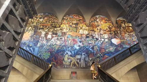 先の写真の右正面奥の階段の壁に描かれた、ディエゴ・リベラによる壁画「メキシコの歴史」です。