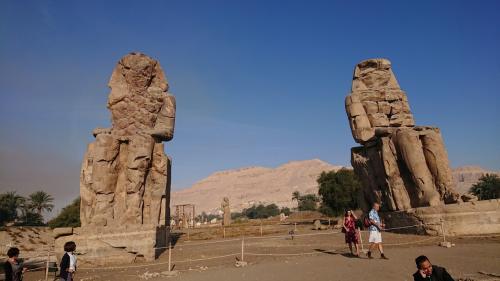メムノンの巨像は一対でたっています。<br />間には王家の達が見えます。