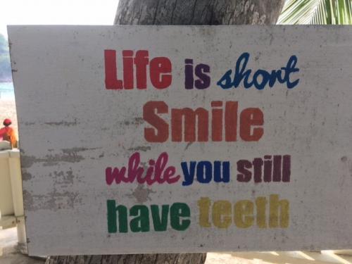 人生は短い!歯がある(健康な)うちに、笑おう(楽しもう)!という看板が、ヤシの木にぶら下がってた。