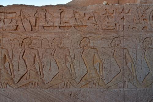 ラムセス2世像の足元のレリーフには、アブシンベル地方を征服して捕虜にしたヌビア人を描いており、首には捕虜同士を繋げているロータス(睡蓮)のひもが巻き付けられている。<br /><br />このアブシンベル地方はエジプト最南端で、ここに住むヌビア人は人種的にもアラブ系とは異なり、アフリカン(いわゆる黒人)に属するとのことで、レリーフにもその特徴が出ている。<br />