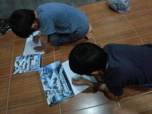 宿に戻ってお絵描き大会。ガンダムの模写に励む男子二名。<br /><br />もともと、お絵描き好きな子たちなのですが、旅行中は無理だと<br />思い込んでいたようで、「紙も色鉛筆も持ってきとうよ」と告げると、<br />嬉々として描き始めました。