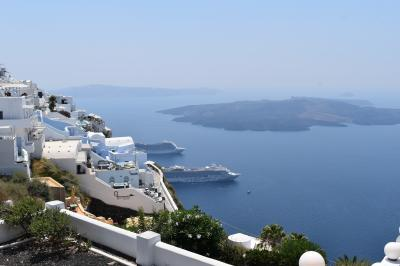 島は海底火山の噴火で形成されたカルデラで、火口と外輪山の間に海水が入り、現在のような姿となった。外輪山の火口側はいずれも急斜面となっており、そこに建物が密集している。元々はギリシャの貿易商が停泊中の自分たちの船を見下ろせるよう、海側の崖に商館や集落を建設したのがはじまりで、その後は住居、そして観光用のホテルなどに転用された。<br />頼んでおいた車でつづら折りの坂道を登り、ホテルのあるフィロステファニに到着。港近辺の雰囲気からは一転し、駐車場から海方面を見ればこの光景。海と山、両方をいいとこ取りのような眺めが楽しめるのが実にすばらしい。ここなら3年くらいはサバイバルできそう。
