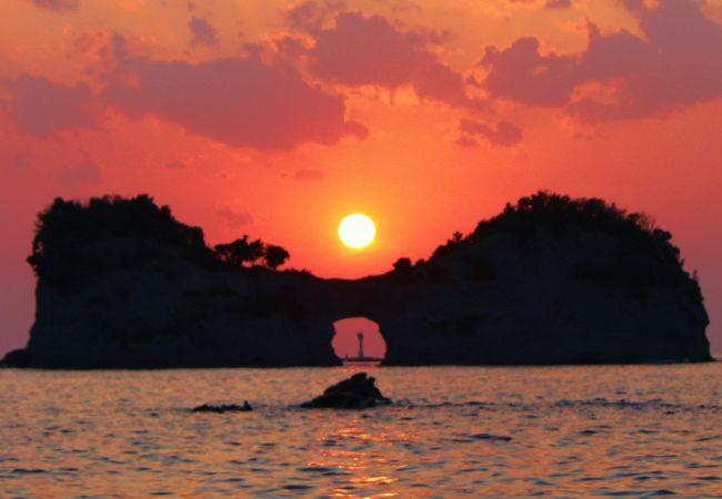 円月島の浸食穴から見える灯台、沈もうとしている太陽