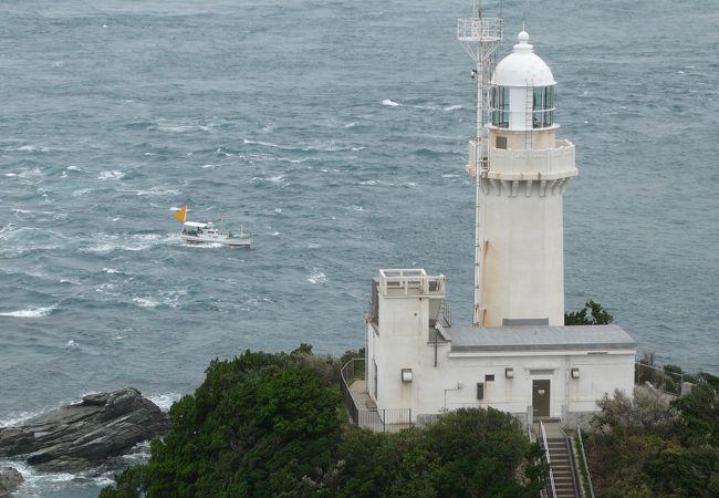 荒波にもまれる釣り船と灯台