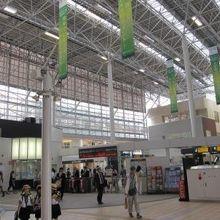 駅構内の風景で、天井が高く一部がガラス張りになっています