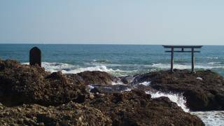 海に向かってたつ鳥居と海水浴場