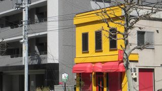 黄色い壁に赤いひさしの小さなケーキ屋さん