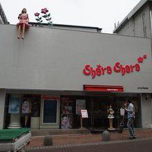 店の看板の上にはかわいい女性の人形が乗っている