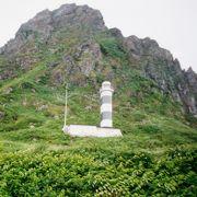 岬の断崖の中腹に縞模様の灯台