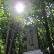 円山原始林をひかえ、木々の中に佇む石碑