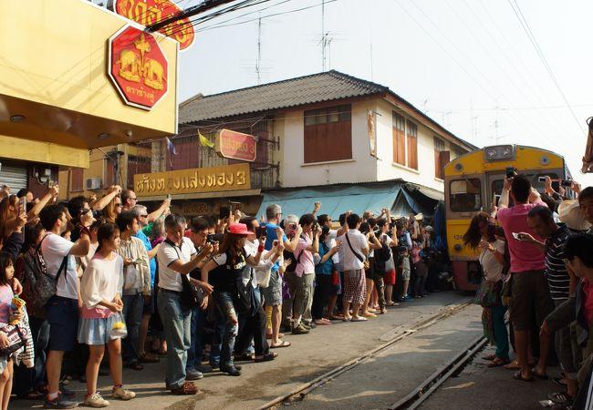 観光客が待ちかまえる中を列車が徐行する。