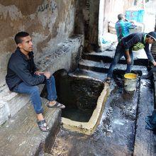 井戸のような場所。水が貯まっていて洗ったり水を汲みに来たり。