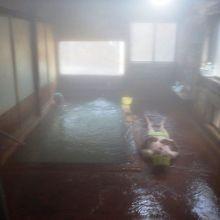 湯船脇に寝て、豊富に湧き出る湯の流れを全身で浴びるトド寝だ