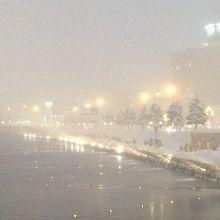 雪が降ってぼんやりしているけど、赤路が灯っている。