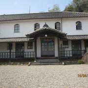 白壁にアーチ型の窓の近代の西洋式の学校の建物です。