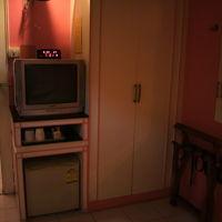 客室内のタンスとテレビ・冷蔵庫です。コップと飲み物があります