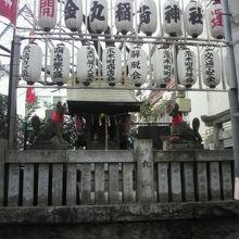 金丸稲荷神社の石柱の側壁と提灯です。壁越しに社が見えます。