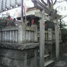 金丸稲荷神社の入口です。社、石柱側壁、鳥居、提灯が見えます。