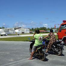 着陸した飛行機の駐機を待つ人々