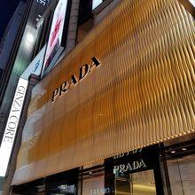 14587dcf6ddf ご存知、イタリアミラノに本店も構えるプラダの銀座店は、銀座4丁目交差点近くのテナントビルGINZACOREの隣にあります。黄金色の外観とロゴは 抜群の存在感があります。