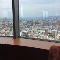 ホテルの窓から大阪の街並みを見渡しています。
