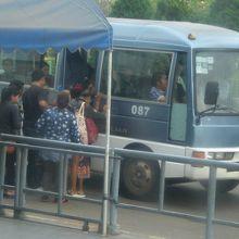 タイとラオスの国旗を付けている国境間ミニバスです。乗客が多い