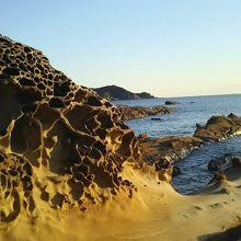 夕日に染まる岩