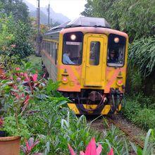 鄙びた景色の中を走るオレンジ色の列車