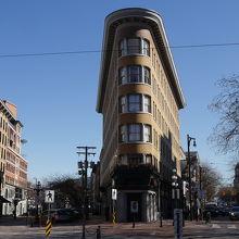 細長いビルが交差点に建っています