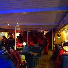 防寒着を着て、船内で待つ人や