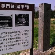 当時の門の写真を示すパネルと石碑があります