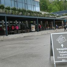 チケット売り場を示す表示が道路に出ています。前方の建物1階で