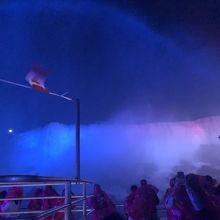 青や赤にライトアップされた滝の上に掛かる虹