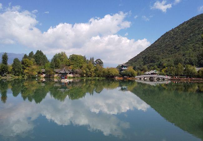 白い雲と緑の山と玉龍雪山の山影を水面に映す黒龍潭です。