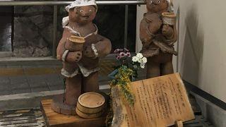 狸が見つけた、湯!頭に手ぬぐいを巻いた2匹の狸の像がある湯河原駅