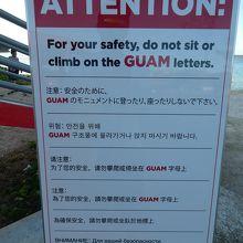 「GUAM」の文字のモニュメントの注意書