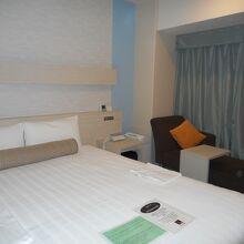 広いベッドと眺望を楽しむためのソファーがある部屋