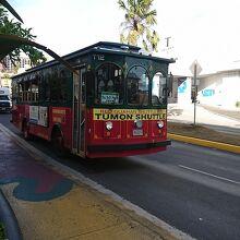 ホテル通りを走る赤いシャトルバス
