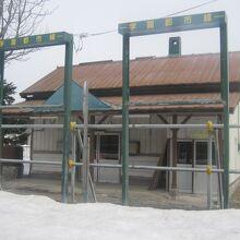 旧ホーム側から、駅名標の遺構越しに眺める旧駅舎の様子