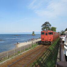 道の駅の前から電車と雨晴海岸と立山連峰