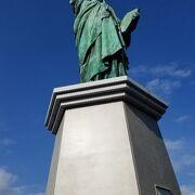 青空を背景に緑青色の女神像がくっきりと映える